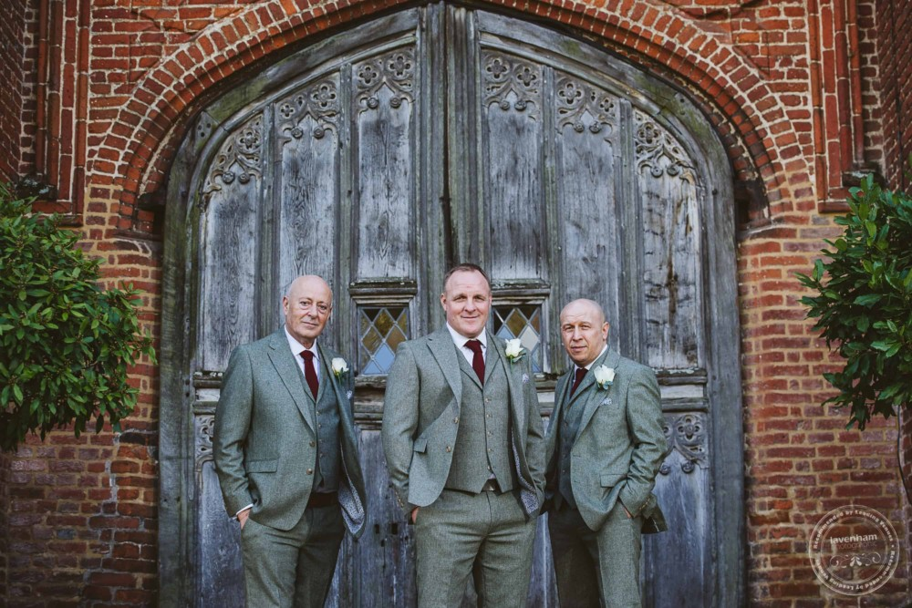 Photograph of the groomsmen in front of one of Leez Priory's impressive Tudor  carved wooden doors