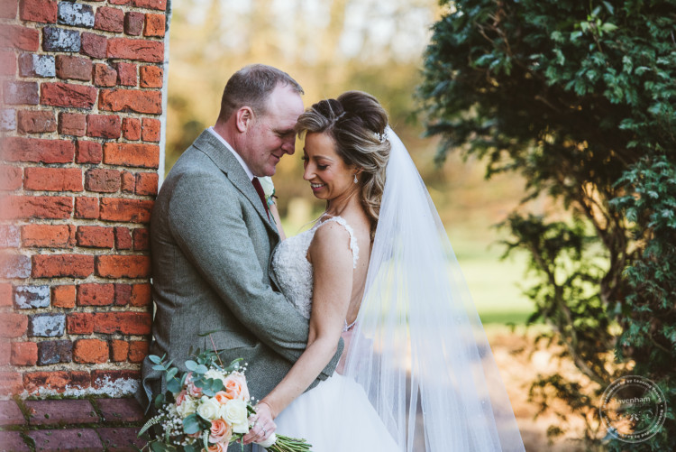 Bride and groom at Leez Priory's tower share a tender moment