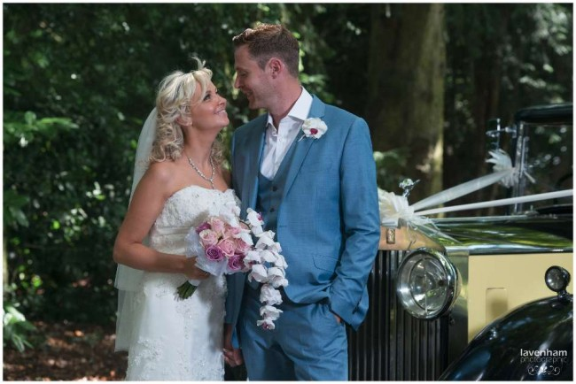 Bride and groom with wedding car, looking to eachother, creative remote lighting