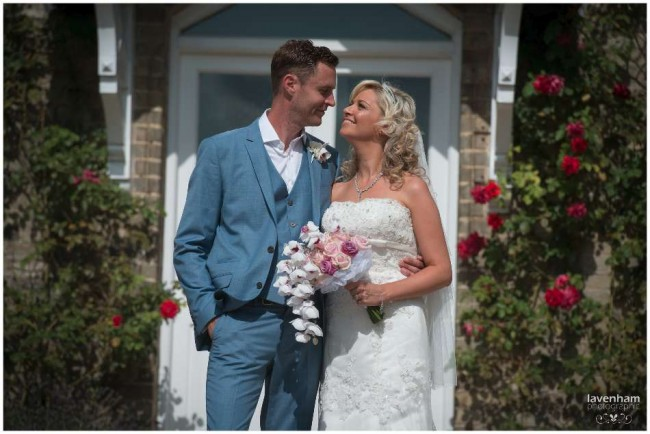 Photography of bride and groom with doorway and red roses behind, Smeetham hall wedding
