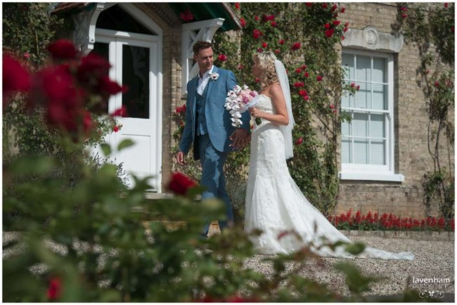 Bride and groom photographed walking, through red roses at front of Smeetham hall