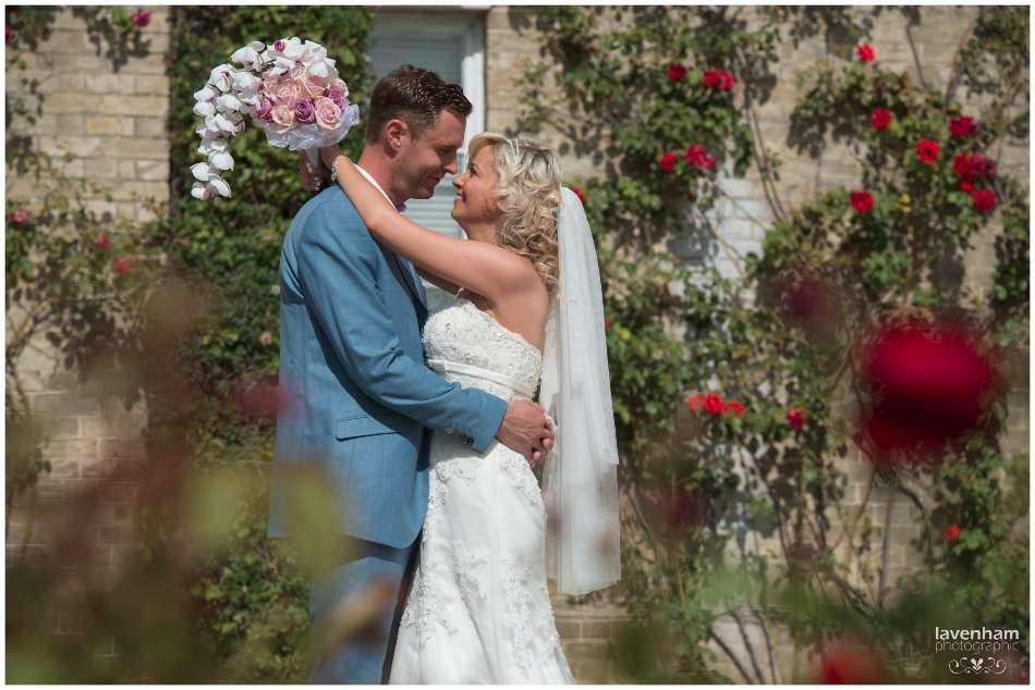 Bride and groom photographed through red roses at front of Smeetham hall