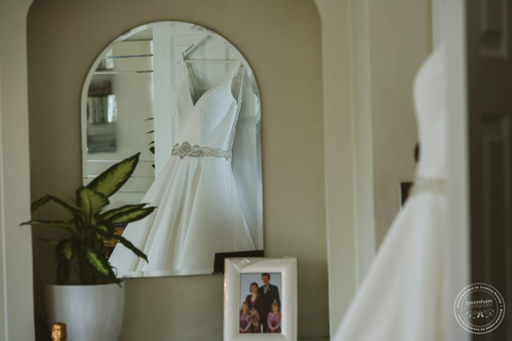 Wedding dress hangs in the bride's house in the morning of the weddingq