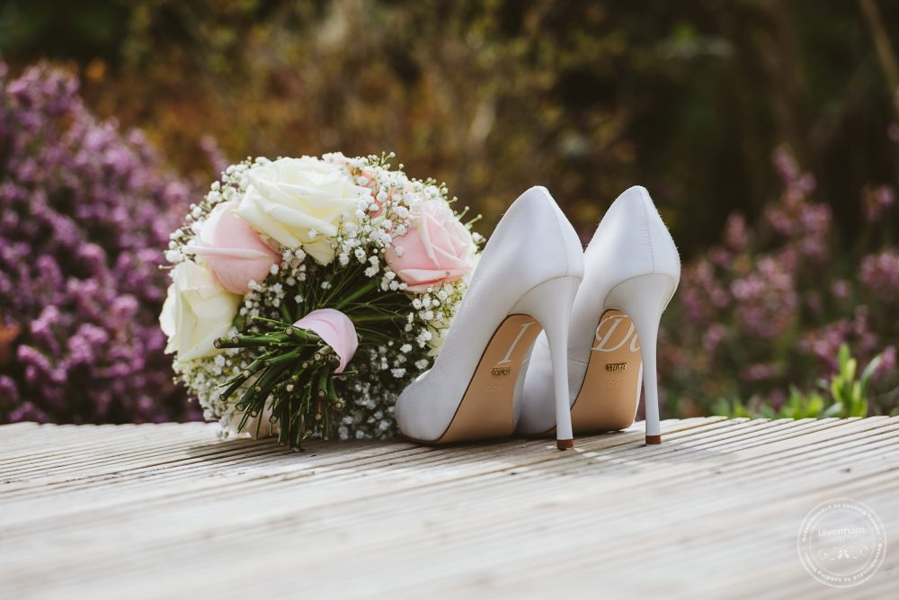 The bride's wedding shoes photographed in detail in front of pink flowerbeds