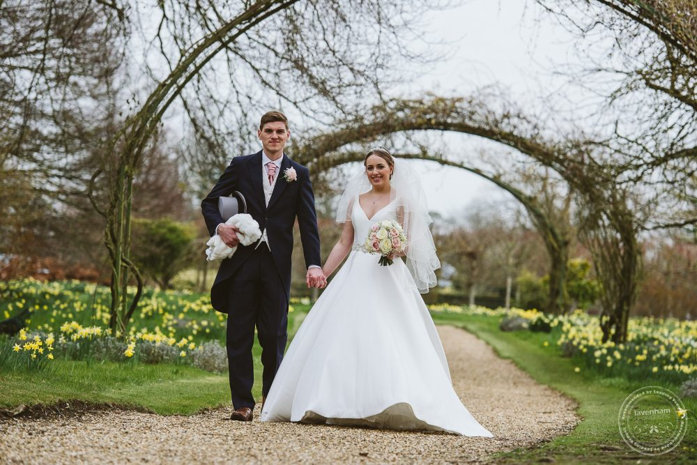 Casual wedding photography as the bride and groom take a stroll in the grounds at Chippenham park
