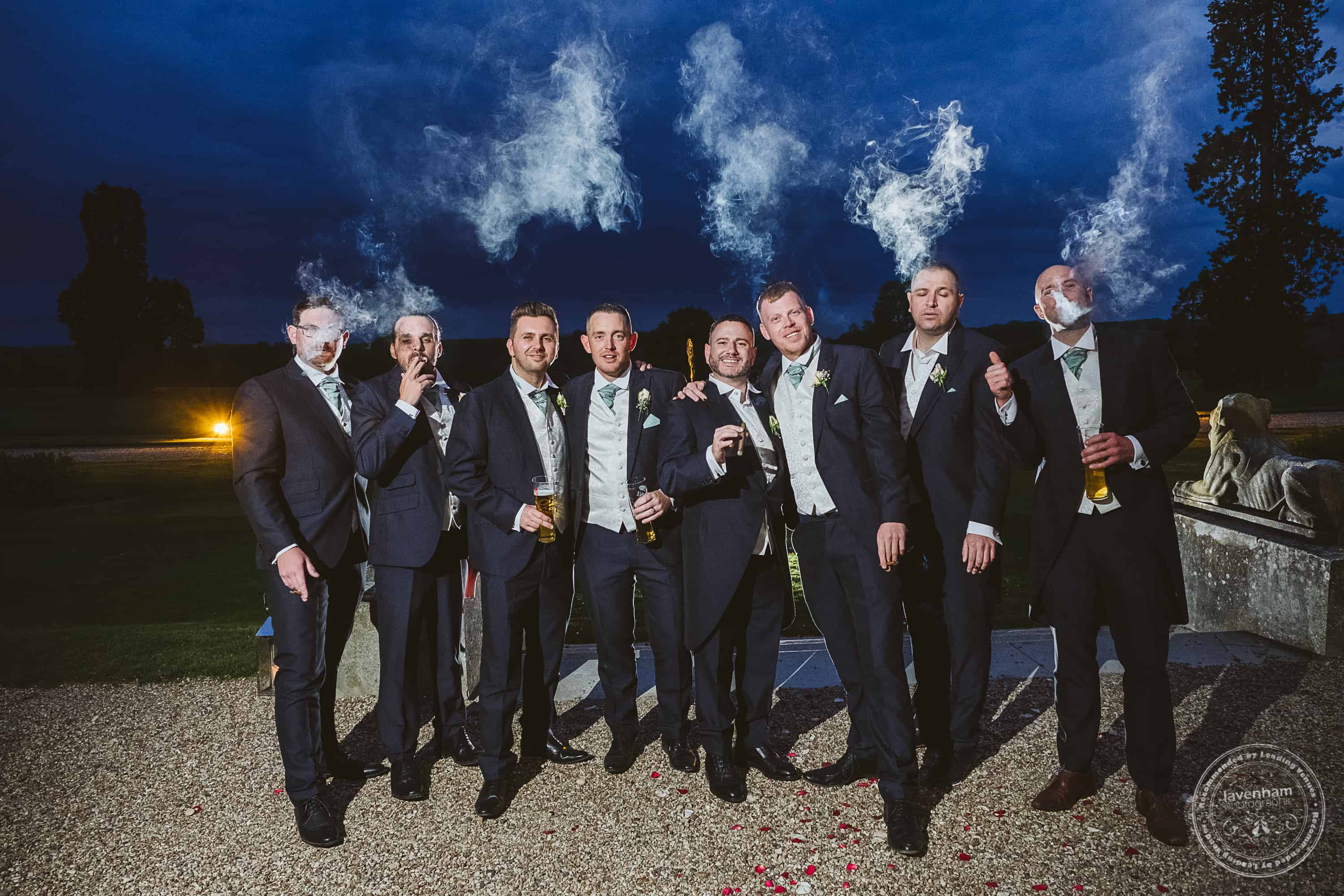 Evening photo of the groomsmen with cigars, their smoke picked out by off-camera flash lighting