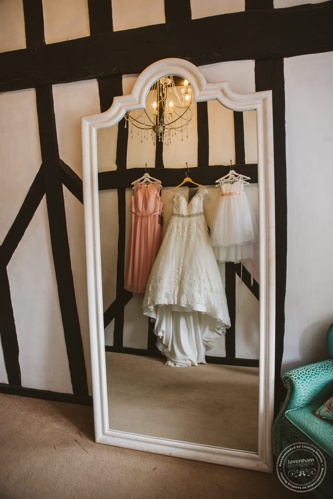 Wedding Dress hanging with bridesmaids dresses, photographed in a mirror