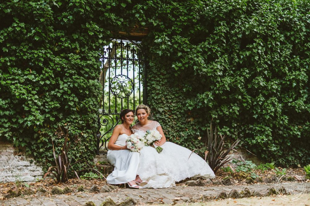 The girls sitting at the old gate with ivy covered wall