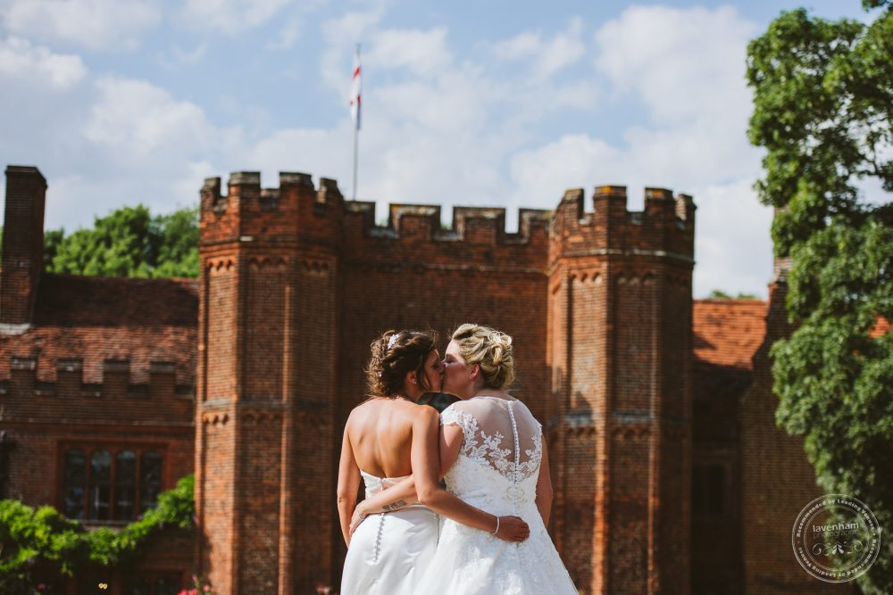 The two brides look on, to the front of Leez Priory. Showing the summer with blue sky, sun on the building and bushy trees