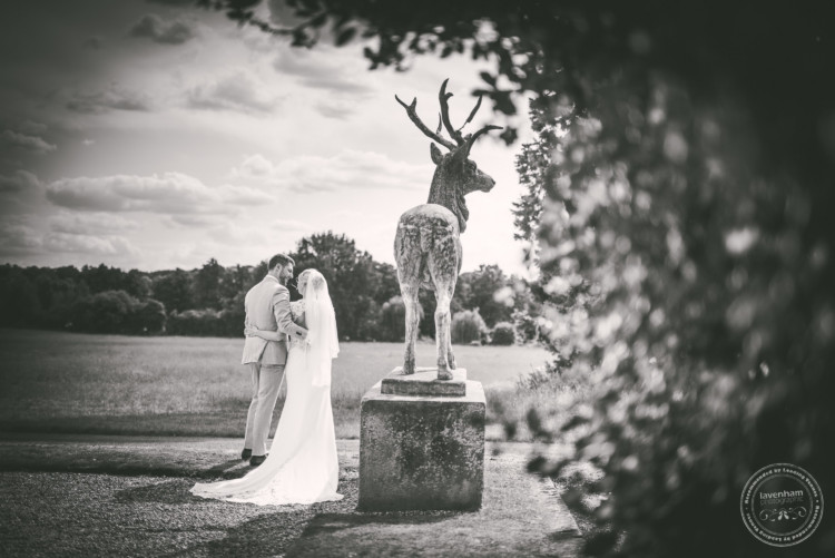 Bride and groom photographed having a quiet moment by one of the stag statues at Gosfield Hall. Casual, relaxed wedding photography