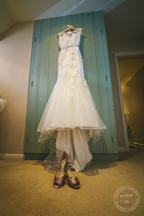 Photograph of Brides wedding dress hanging on green wardrobe door with shoes