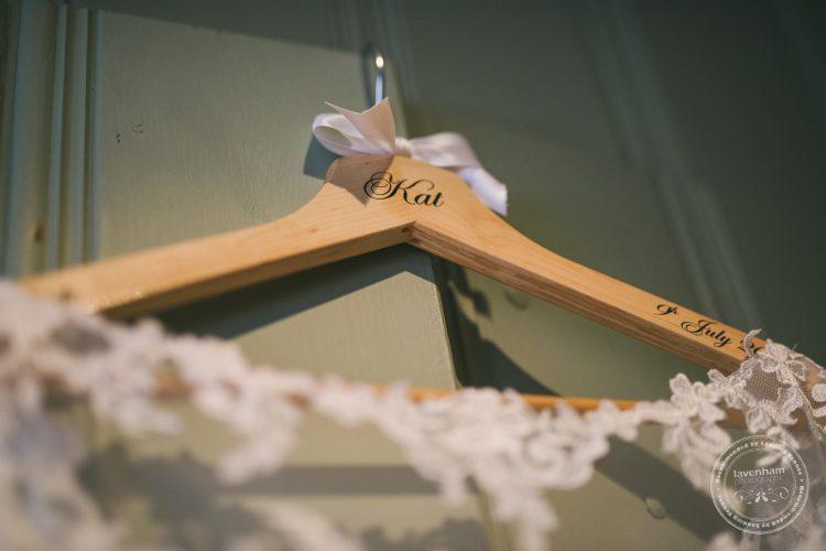 Detail of name personalised hanger, Photograph of Brides wedding dress hanging on green wardrobe door