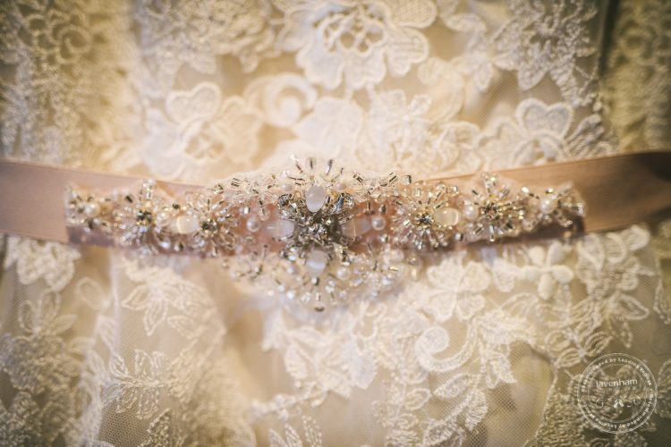 Detail photograph of wedding dress lace and brooch
