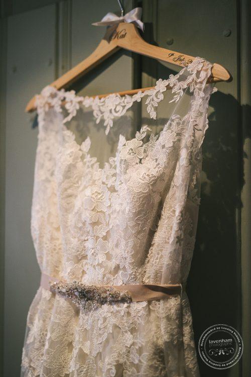 Photograph of Brides wedding dress hanging on green wardrobe door