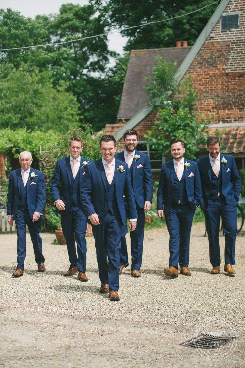 Groom with groomsmen, walking, at Preston Priory Barn