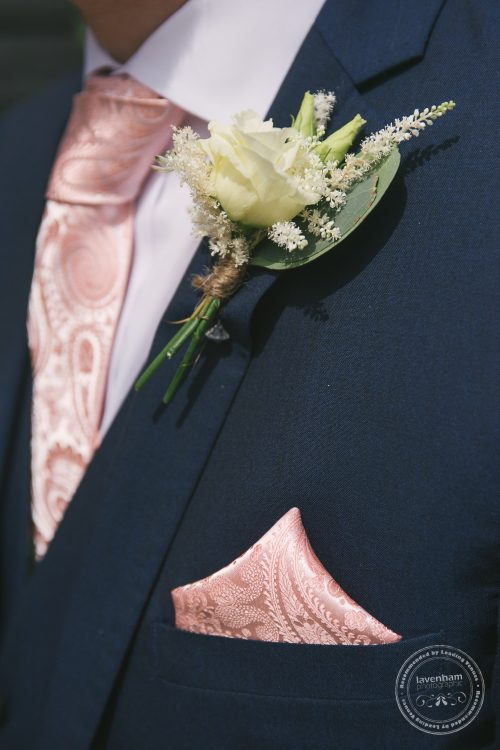 Detail photograph of groom's wedding pink tie, napkin and buttonhole flower