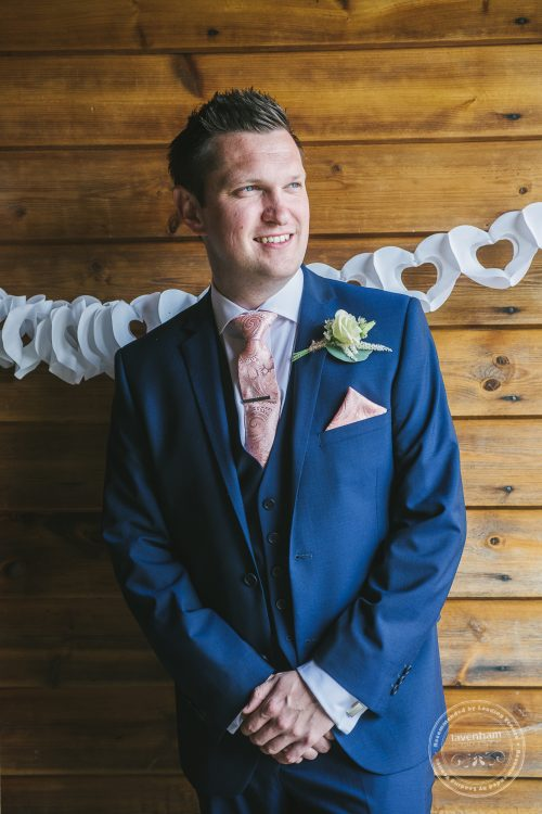 Portrait photograph of the groom against wooden wall, Preston Priory Barn