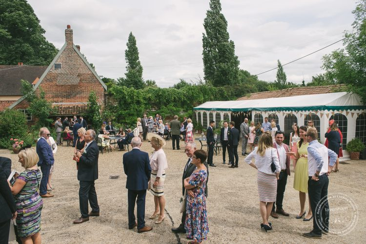 Photography of wedding guests gathering in courtyard at Preston Priory Barn