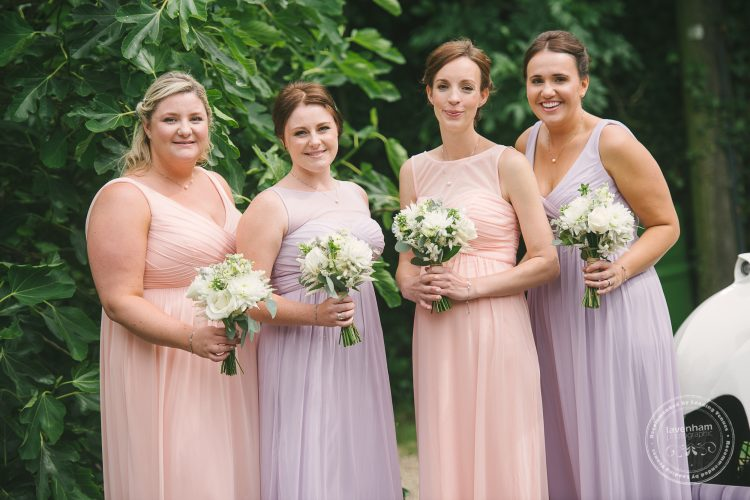 Photography of the bridemaids before the wedding ceremony at Preston Priory Barn. Alternating bridemaids dress colours