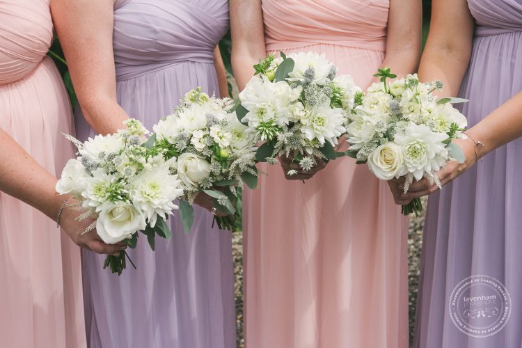 Photography of the bridemaids' wedding bouquet's before the wedding ceremony at Preston Priory Barn. Alternating bridemaids dress colours