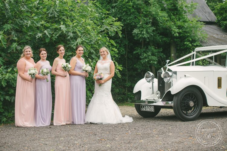 Photograph of bride with bridemaids and Rolls Royce wedding car