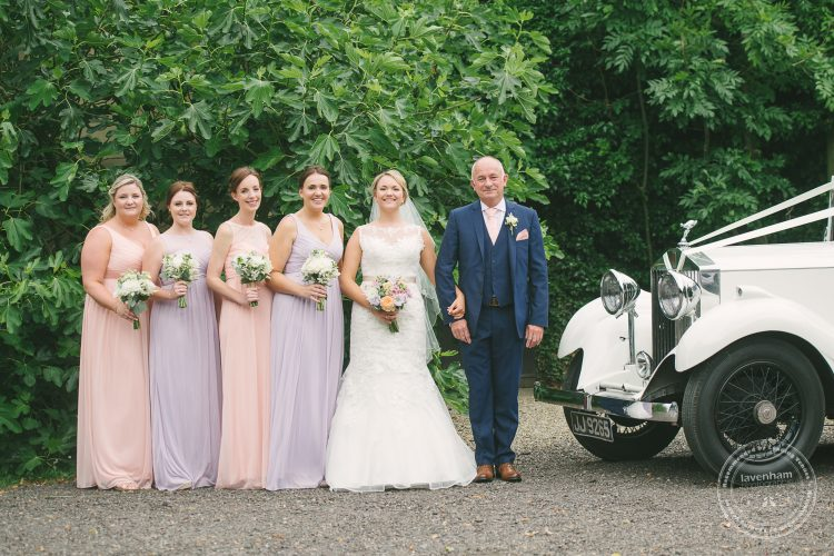 Photograph of bride with bridemaids and father, with Rolls Royce wedding car