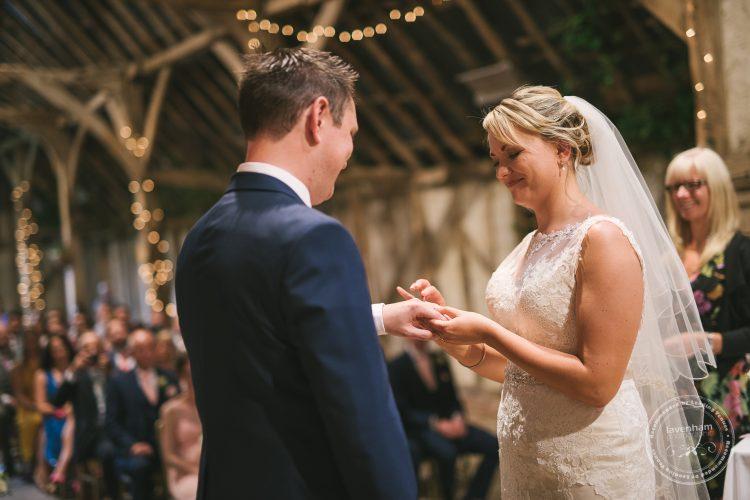 Bride and groom exchange rings at Preston Priory Barn wedding