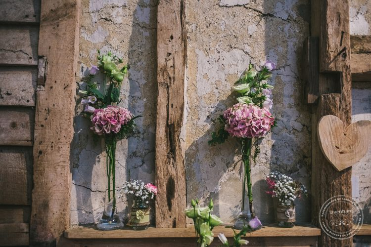 Photography of wedding details at Preston Priory Barn - jars and vases of flowers in Barn