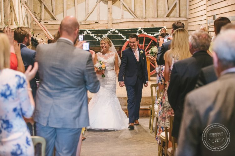Bride and groom walking back down aisle after getting married
