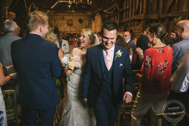 Bride and groom laughing, walking back down aisle after getting married