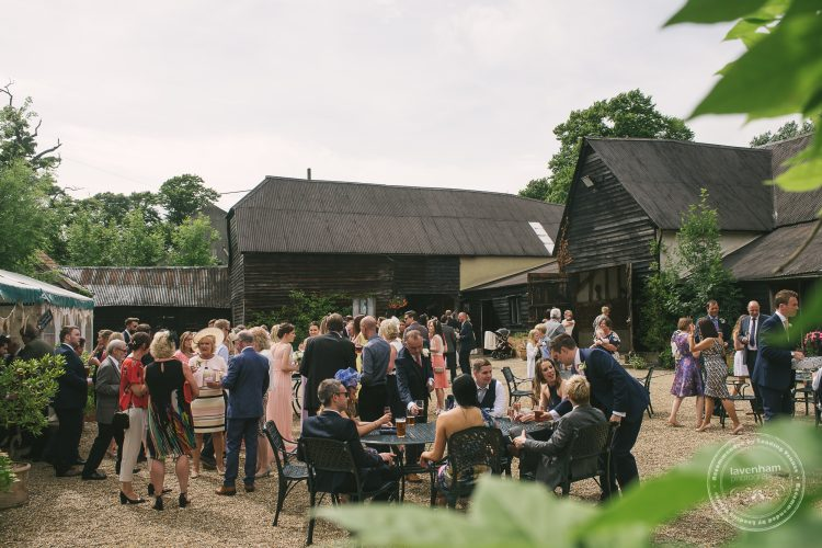 Wedding guests mingling in courtyard at Preston Priory Barn