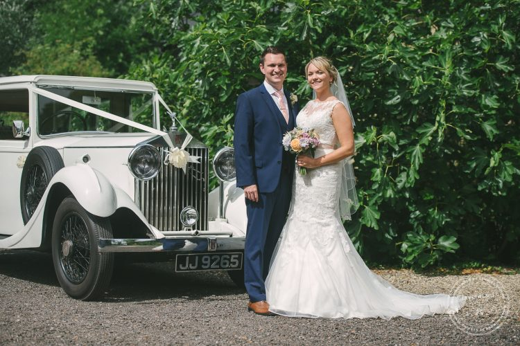 Bride and groom photographed with classic Rolls Royce