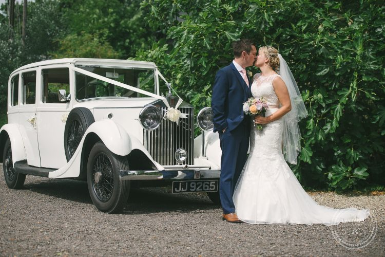 Bride and groom photographed kissing with classic Rolls Royce at Preston Priory Barn