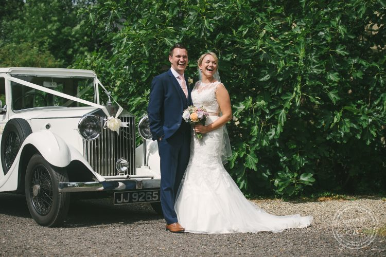 Bride and groom laughing with classic Rolls Royce at Preston Priory Barn