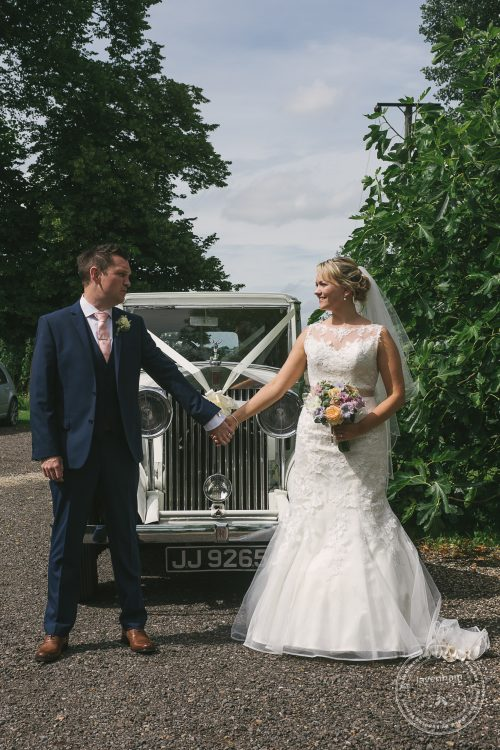 Photography of wedding couple holding hands in front of Rolls Royce