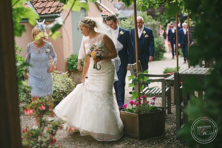Bride walking through vines at Preston Priory Barn