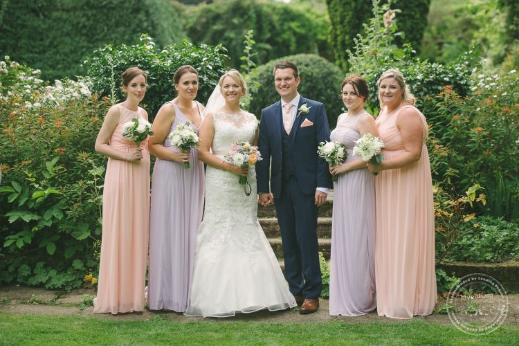 Group photograph of wedding party, bride, groom and bridesmaids at Preston Priory Barn