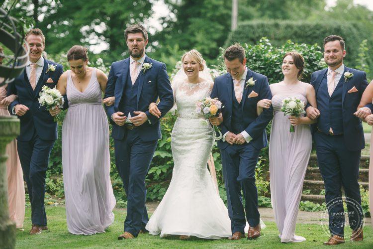 Group photograph of wedding party, bride, groom, ushers and bridesmaids walking at Preston Priory Barn