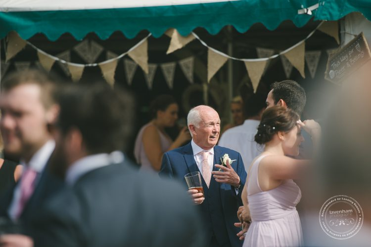 Guests chatting at wedding with bunting behind