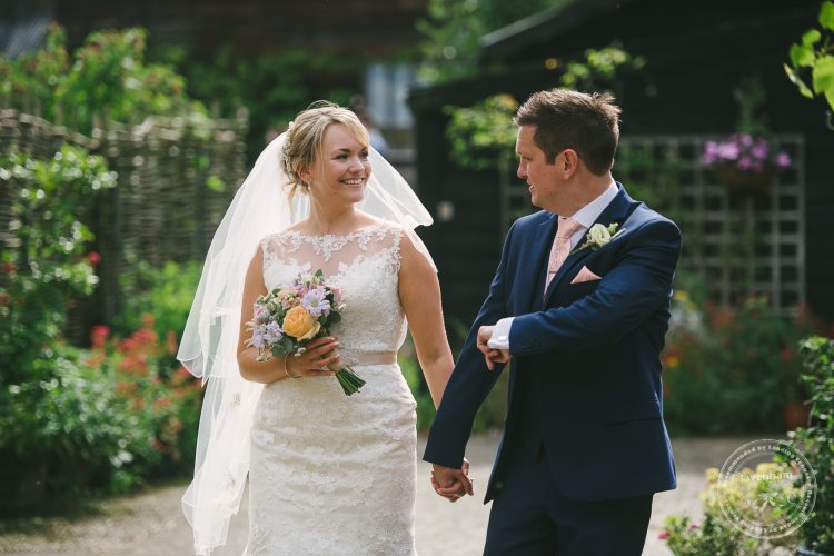 Casual wedding photo of bride and groom walking