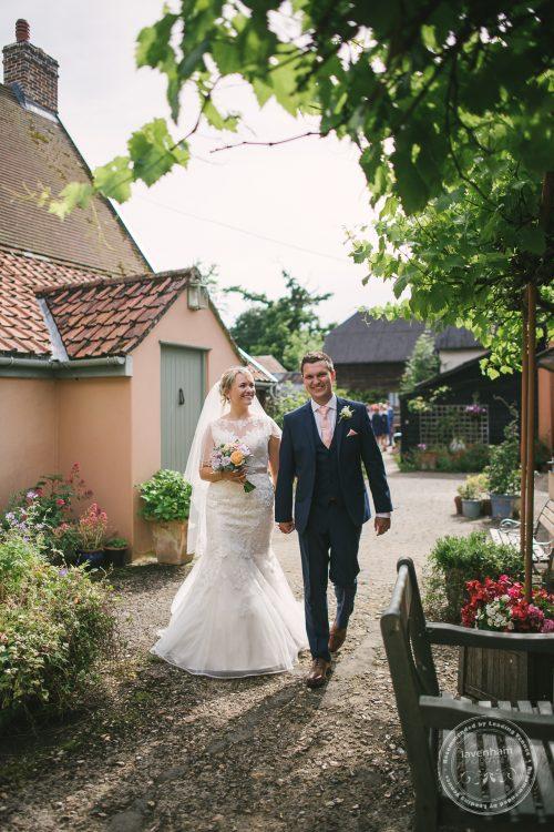 Casual wedding photo of bride and groom walking at Preston Priory Barn