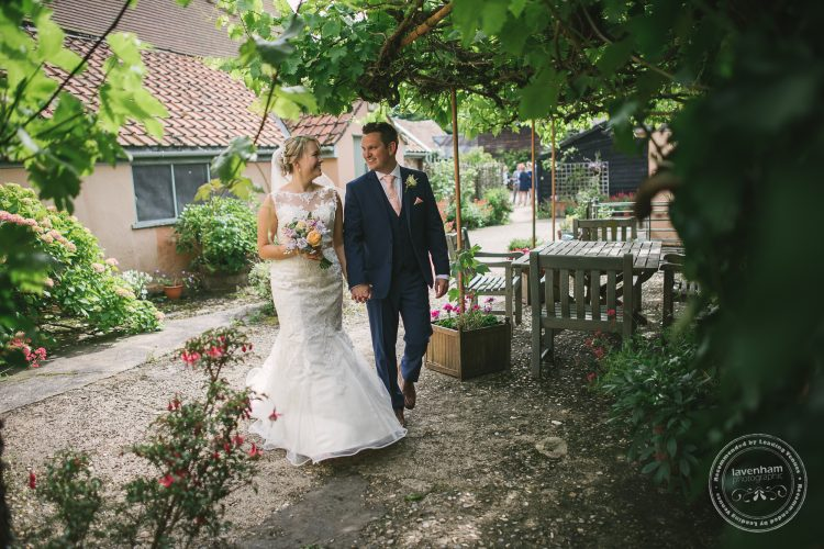 Casual wedding photo of bride and groom walking through grapevines at Preston Priory Barn