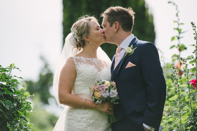 Wedding photo of Bride and groom kissing in garden at Preston Priory Barn