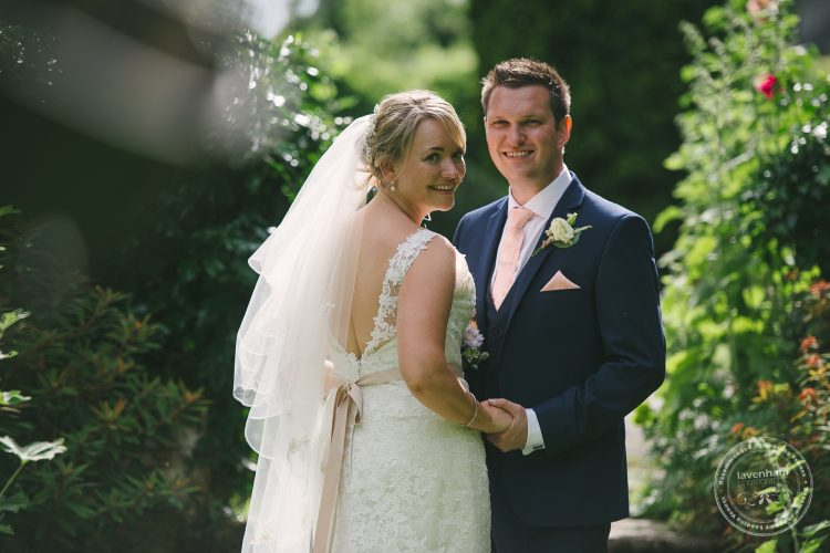 Wedding photo of Bride and groom in garden with sun dial at Preston Priory Barn