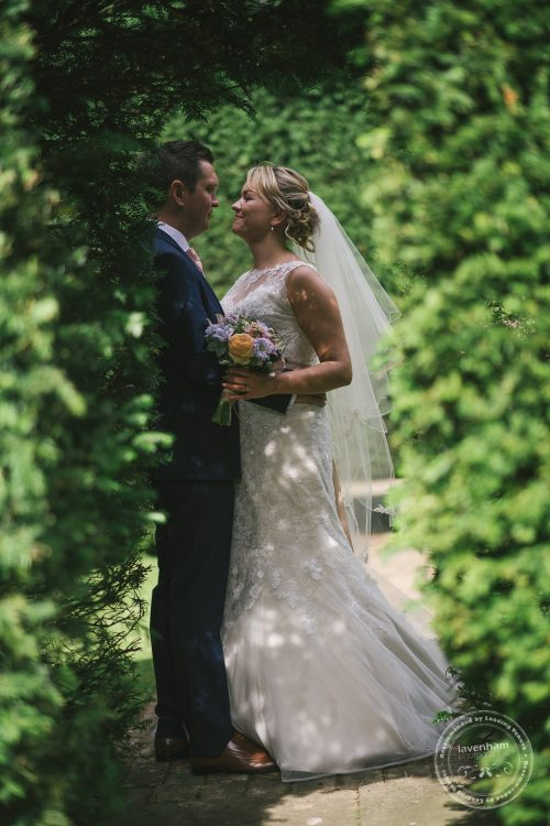 Wedding couple shot through archway in hedge at Preston Priory Barn
