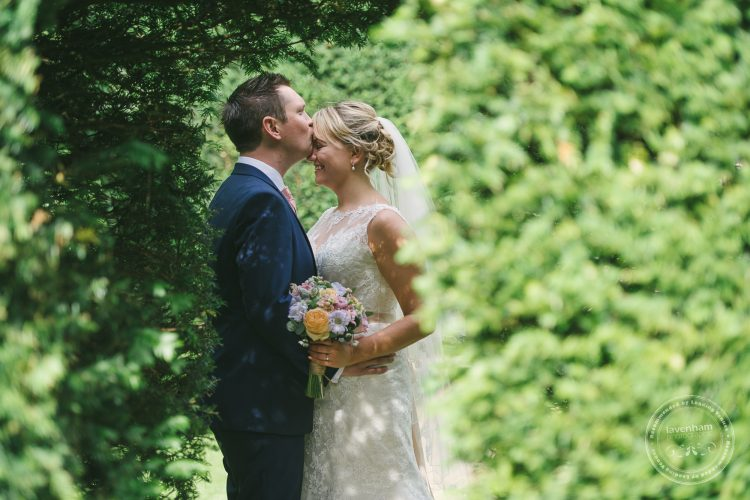 Groom kissing bride on forehead through archway in hedge at Preston Priory Barn