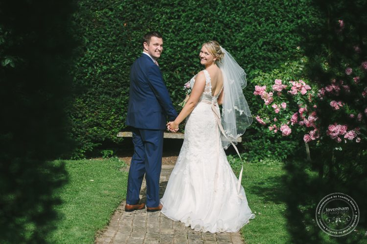 Wedding couple photographed walking away, shot through archway in hedge at Preston Priory Barn