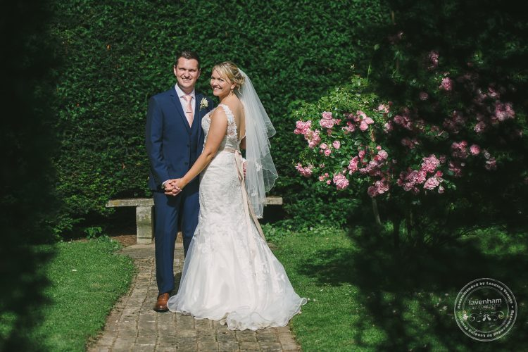 Wedding couple photographed shot through archway in hedge at Preston Priory Barn