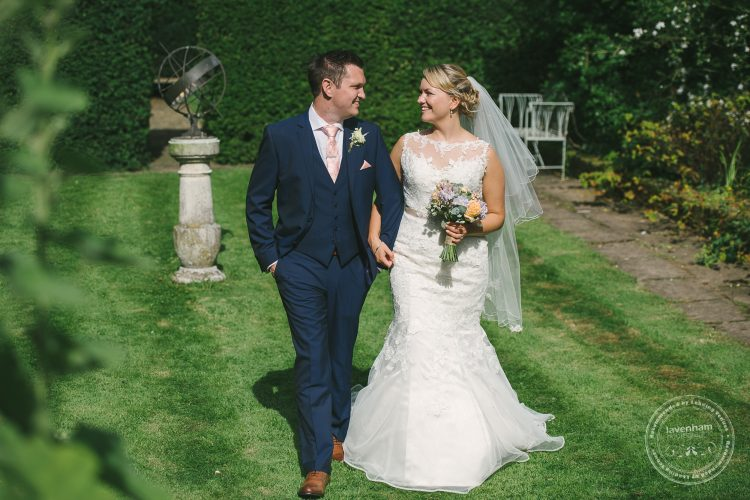 bride and groom walking through garden with sun dial at Preston Priory Barn