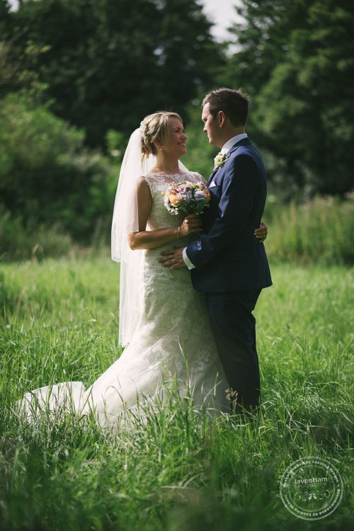 Wedding couple standing in long grass at Preston Priory Barn